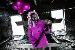 Zombie girl with a bunch of pink balloons. In a pretty pink coat Stock Photos