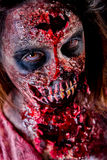 Zombie girl closeup. Closeup of zombie girl staring with bloody makeup and latex prosthesis royalty free stock photos