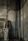 Zombie girl with loong hair holding knife. Zombie girl with loong hair in an abandoned building holding knife Royalty Free Stock Photography
