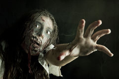 Zombie girl. Girl with zombie make-up in a dark background Stock Photos