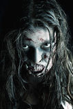 Zombie girl. Girl with zombie make-up in a dark background Stock Images