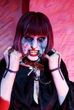 Zombie girl with metal chain in teeth Stock Image