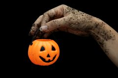 Zombie Halloween hand and pumpkin isolate on black bacground stock images
