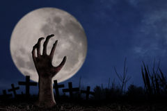Zombie hand on graveyard. Spooky graveyard with zombie hand coming out of the ground Stock Image
