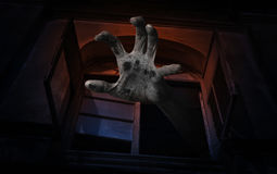Zombie hand rising out from old ancient window, Spooky background, Halloween concept stock photography