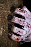 Zombie hand scratching a wooden surface Stock Images