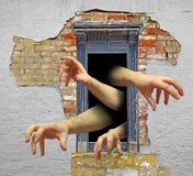 Zombie hands in door Stock Photo