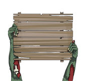 Zombie hands holding up an old wooden plank board Royalty Free Stock Photo