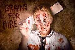 Zombie holding bright light bulb. Brains for hire Royalty Free Stock Photography