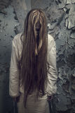 Zombie with loong hair in an abandoned building Royalty Free Stock Photography