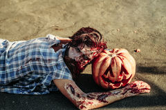Zombie man lies on pumpkin Royalty Free Stock Photos