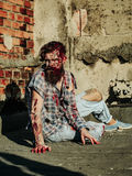 Zombie man sits on asphalt. Bearded zombie man with beard creepy vampire or bloody war soldier with wounds and red blood sits on asphalt road Stock Image