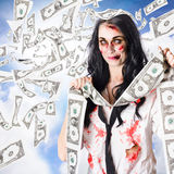 Zombie person with falling 1 dollar US bank notes. Female zombie person celebrating massive accumulated wealth in a depiction of the saying TO BE THE RICHES Stock Photo