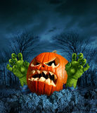 Zombie Pumpkin. Halloween greeting card with copy space as a scary surprise creepy jack o lantern with monster green hands rising from the dead on a dark cold royalty free illustration