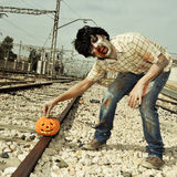Zombie putting a carved pumpkin on the railroad tracks Stock Photography