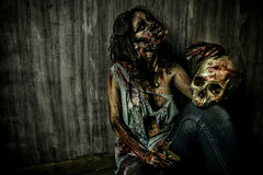 Zombie and skull. Frightening bloody zombie girl with a skull. Halloween Royalty Free Stock Photos