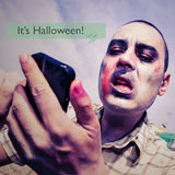 Zombie with a smartphone and the text message it is halloween Stock Images