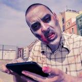 Zombie spaventoso che per mezzo di un computer della compressa, con un effetto del filtro Immagini Stock Libere da Diritti