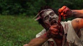 Zombie spaventoso che si siede sull'erba verde e sulla mano strappante della carne cruda stock footage