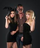 Zombie vampire and witch  in the dark studio. Zombie vampire and witch are standing whith pumpkin in the dark studio Stock Photo