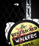 Zombie Walkers Behind Fence Restricted Zone Sign. A walker behind fence with a warning sign Royalty Free Stock Images