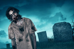 Zombie walking with creepy expression. Graveyard and fog background Royalty Free Stock Photo
