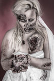 Zombie bride. Is a zombie wearing a wedding dress with hand on heart Stock Image
