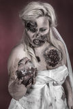 Zombie bride. Is a zombie wearing a wedding dress with hand on heart royalty free stock photo