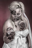 Zombie bride. Is a zombie wearing a wedding dress with hand on heart stock photography