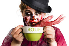 Zombie woman eating hand soup. A woman in zombie costume and make up eating a soup with a human hand Stock Photo