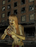 Zombie woman in front of an old hotel Royalty Free Stock Photos