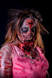 Zombie woman staring. Portrait of zombie woman staring with bloody makeup and latex prosthesis Royalty Free Stock Image