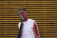 Zombie on wooden background. makeup. halloween concept. Young guy in makeup. zombie. lacerated wounds. on wooden background. halloween concept. caught zombies royalty free stock image