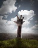 Zombiehand, die aus sein Grab herauskommt Lizenzfreie Stockfotografie