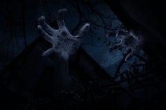 Zombiehand, die heraus vom alten Schmutzschloss über totem Baum steigt Stockfoto