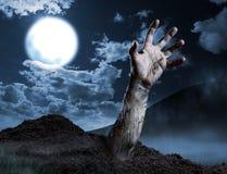 Zombiehand die uit zijn graf komen Stock Foto's