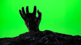 Zombiehand, die vom Grundgrab auftaucht Ein grimmiger Minireaper, der eine Sense anhält, steht auf einem Kalendertag, der glückli stock footage