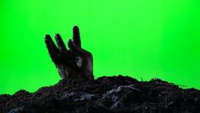 Zombiehand, die vom Grundgrab auftaucht Ein grimmiger Minireaper, der eine Sense anhält, steht auf einem Kalendertag, der glückli stock video