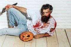 Zombiemann mit Halloween-Kürbis Stockfotos