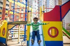 Zomer, kinderjaren, vrije tijd, vriendschap en de gelukkige mensenconcept - gleed weinig jongen op kinderenspeelplaats van de heu royalty-vrije stock fotografie
