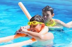 Zomer, twee jongens die een goede tijd hebben bij het zwembad stock foto's
