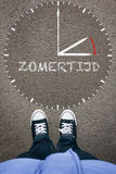Zomertijd, Dutch Daylight Saving Time on asphalt with two shoes, high angle from above. Zomertijd, Dutch Daylight Saving Time clock with pair of legs and shoes stock photography