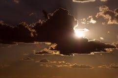 Zon achter wolk stock foto