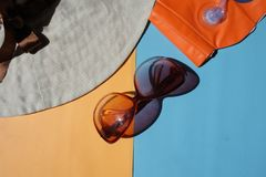 Zon beschermende glazen, hoed op blauwe en oranje achtergrond stock afbeeldingen