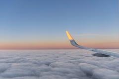 Zon bij de vleugel van een vliegtuig die in zonsopgang vliegen Royalty-vrije Stock Fotografie