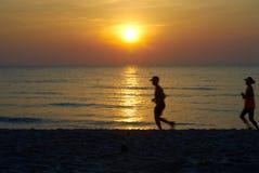 Zon bij strand met het runnen van mensensilhouet dat wordt geplaatst royalty-vrije stock foto