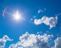 Zon in blauwe hemel met lichte wolken stock foto's