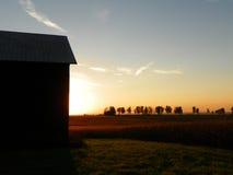 Zon die achter schuur en gebieden van graan in het de herfstplatteland plaatsen Royalty-vrije Stock Fotografie