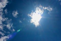 Zon die door wolken in een blauwe hemel glanzen Stock Foto