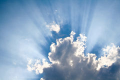 Zon die door wolken glanst Stock Foto